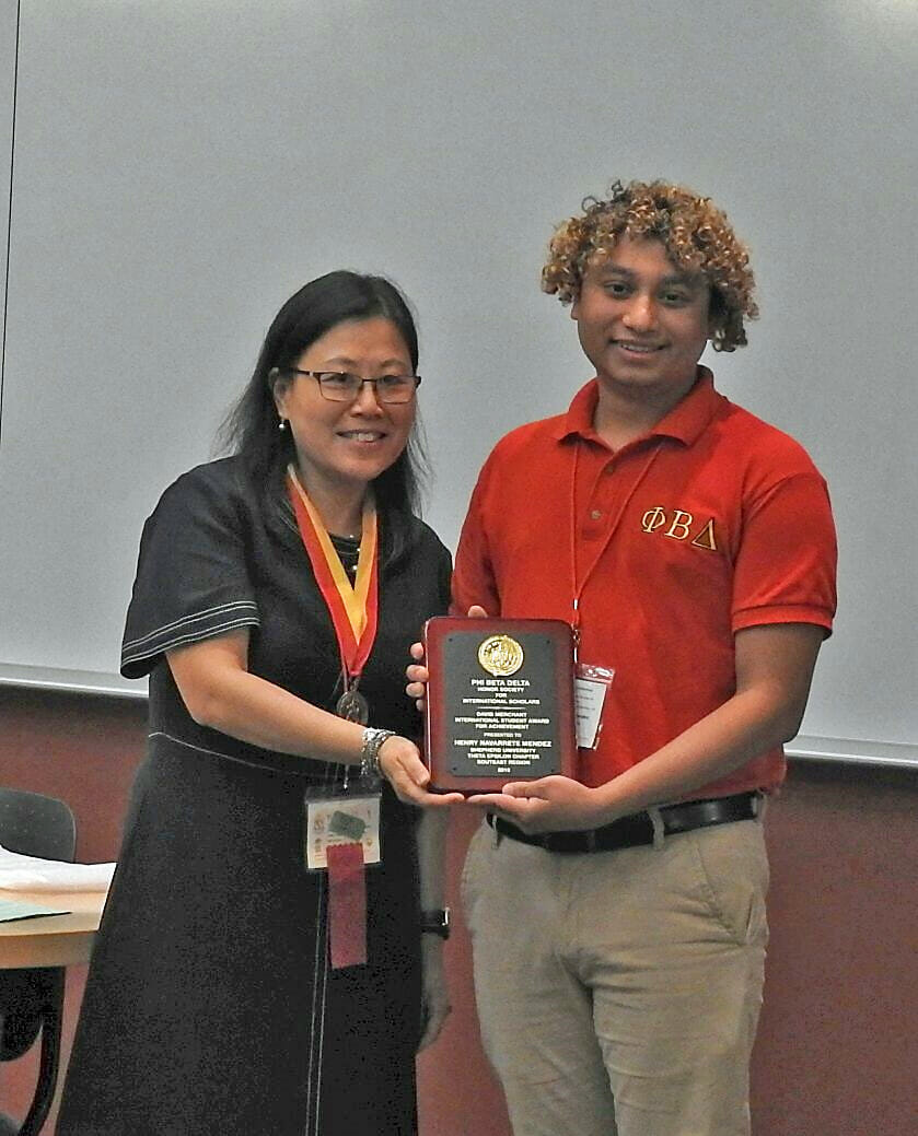 Henry Navarrete Mendez (r.), a computer information technology major from Chantilly, Virginia, received the David Merchant International Student Award for Achievement during the international conference at Shepherd.