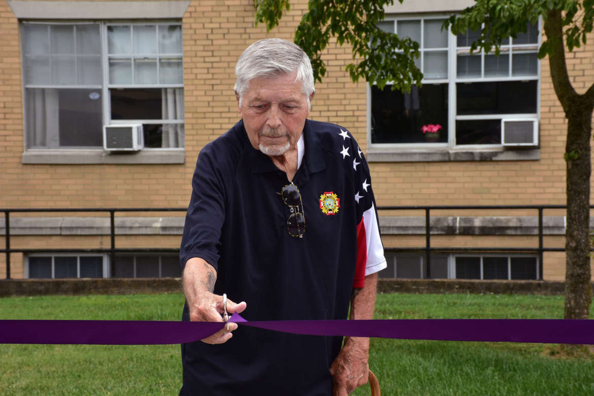 """Wayne """"Bud"""" Casto, U.S. Army and Purple Heart veteran, VFW Post 3522, cuts the ribbon for the new parking space in front of Shepherd University's Gardiner Hall designated for Purple Heart Medal recipients."""