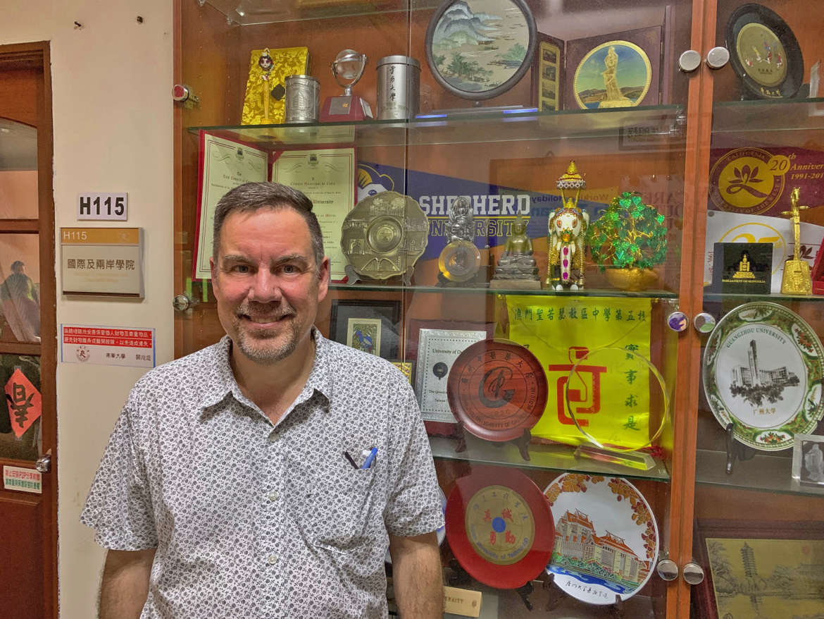 Dr. David Gordon, professor of history, stands in front of a display case at Nanhua University in Chiayi County, Taiwan, where a Shepherd banner is displayed.