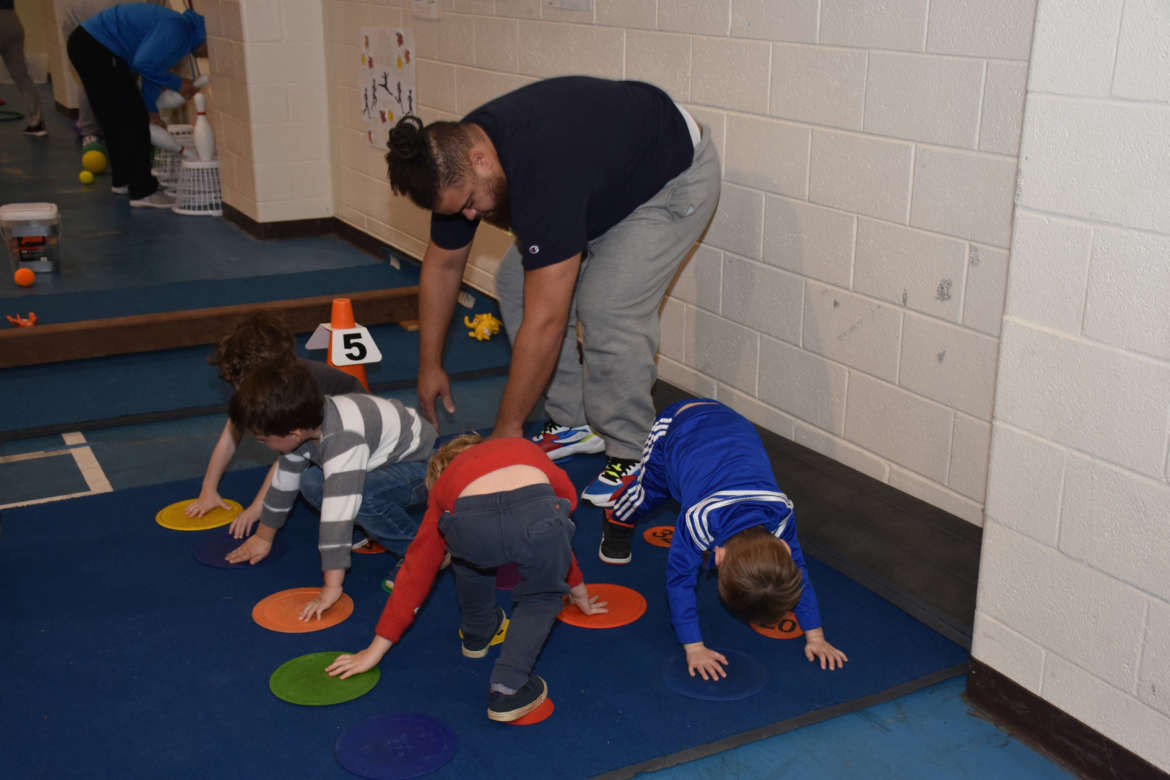 Tyler Ingram, a physical education major from Frederick, Maryland, works with a group of preschoolers from Morgan Academy.