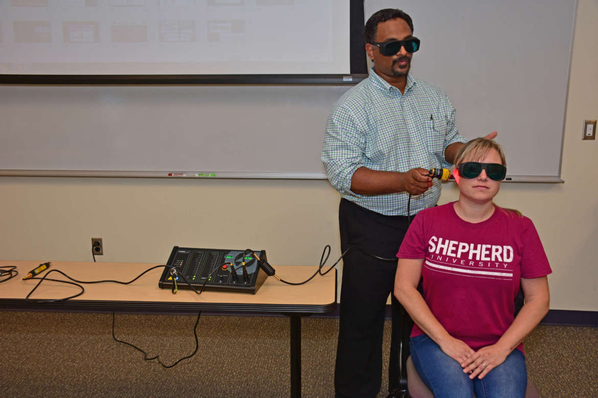 Dr. Praveen Arany, assistant professor, oral biology and biomedical engineering, School of Dental Medicine, Engineering and Applied Sciences, University at Buffalo, New York, demonstrates photobiomodulation therapy on Shepherd University D.N.P. student Amy Evans-Kegley of Charles Town during a class at Shepherd.