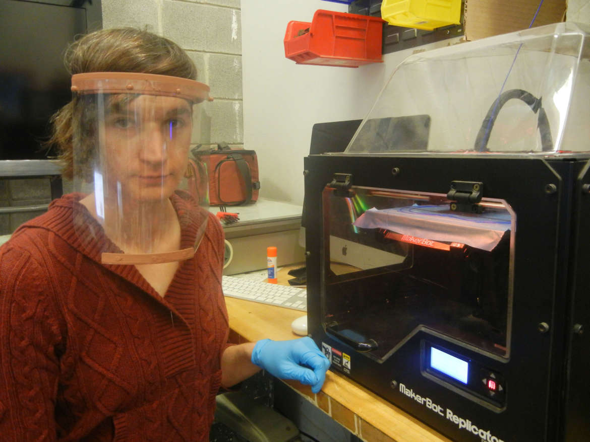Kay Dartt, clinical faculty/3D fabrication manager, models a prototype face shield made in Shepherd's FASTEnER lab.
