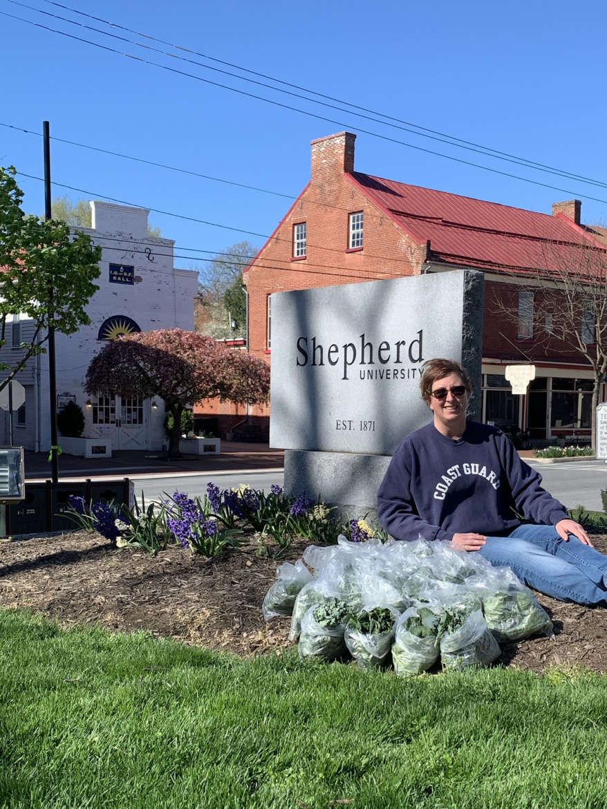Kerri Godfrey, Shepherdstown Shares volunteer, poses with bags of greens harvested at the Shepherd University Agricultural Innovation Center at Tabler Farm that were donated to community members who lost their jobs due to the COVID-19 pandemic.