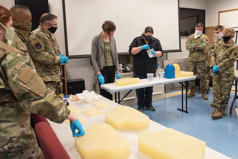 Shepherd University staff, Kay Dartt, 3-D fabrication manager, and Chase Molden, theater technical director, show Airmen with the 167th Airlift Wing how to use silcone molds to make N95 face masks, at the Martinsburg air base, April 20, 2020.