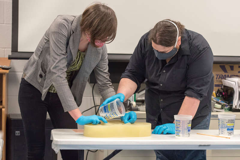 Shepherd University staff, Kay Dartt, 3-D fabrication manager, and Chase Molden, theater technical director, show Airmen with the 167th Airlift Wing how to use silcone molds to make N95 face masks.
