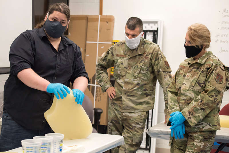 Chase Molden, Shepherd theater technical director, shows Airmen with the 167th Airlift Wing how to use silcone molds to make N95 face masks.