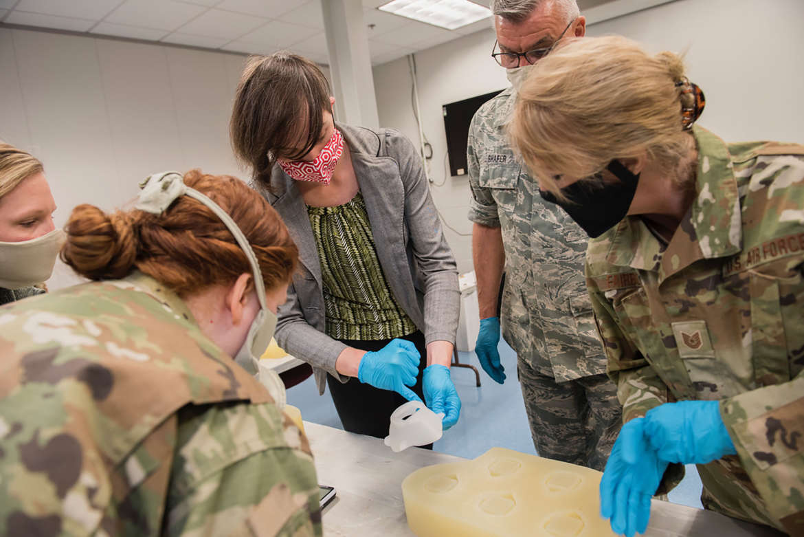 Kay Dartt, 3-D fabrication manager, shows Airmen with the 167th Airlift Wing how to use silcone molds to make N95 face masks.