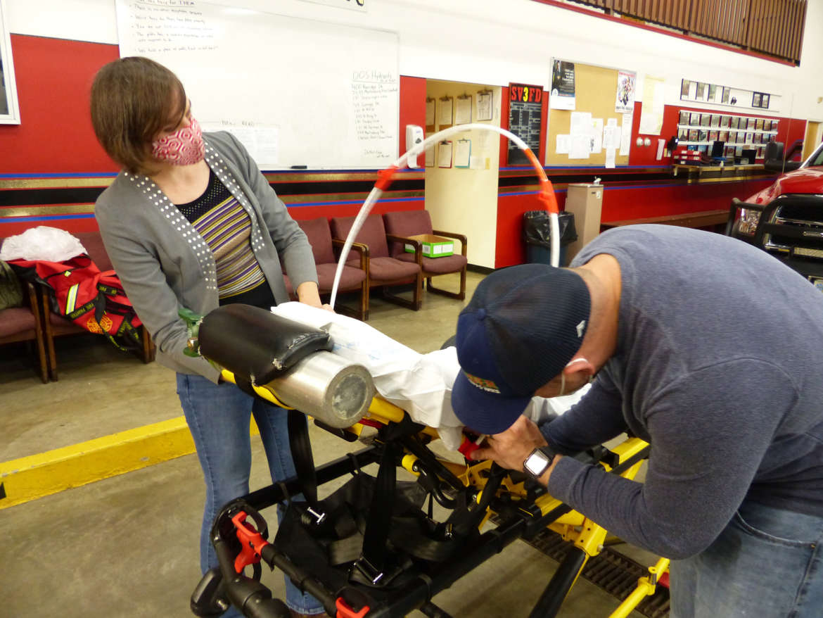 Kay Dartt, Shepherd FASTEnER lab manager, and Marshall DeMeritt, EMS chief, Shepherdstown Fire Department, put a canopy on an ambulance gurney at the Shepherdstown Fire Department.