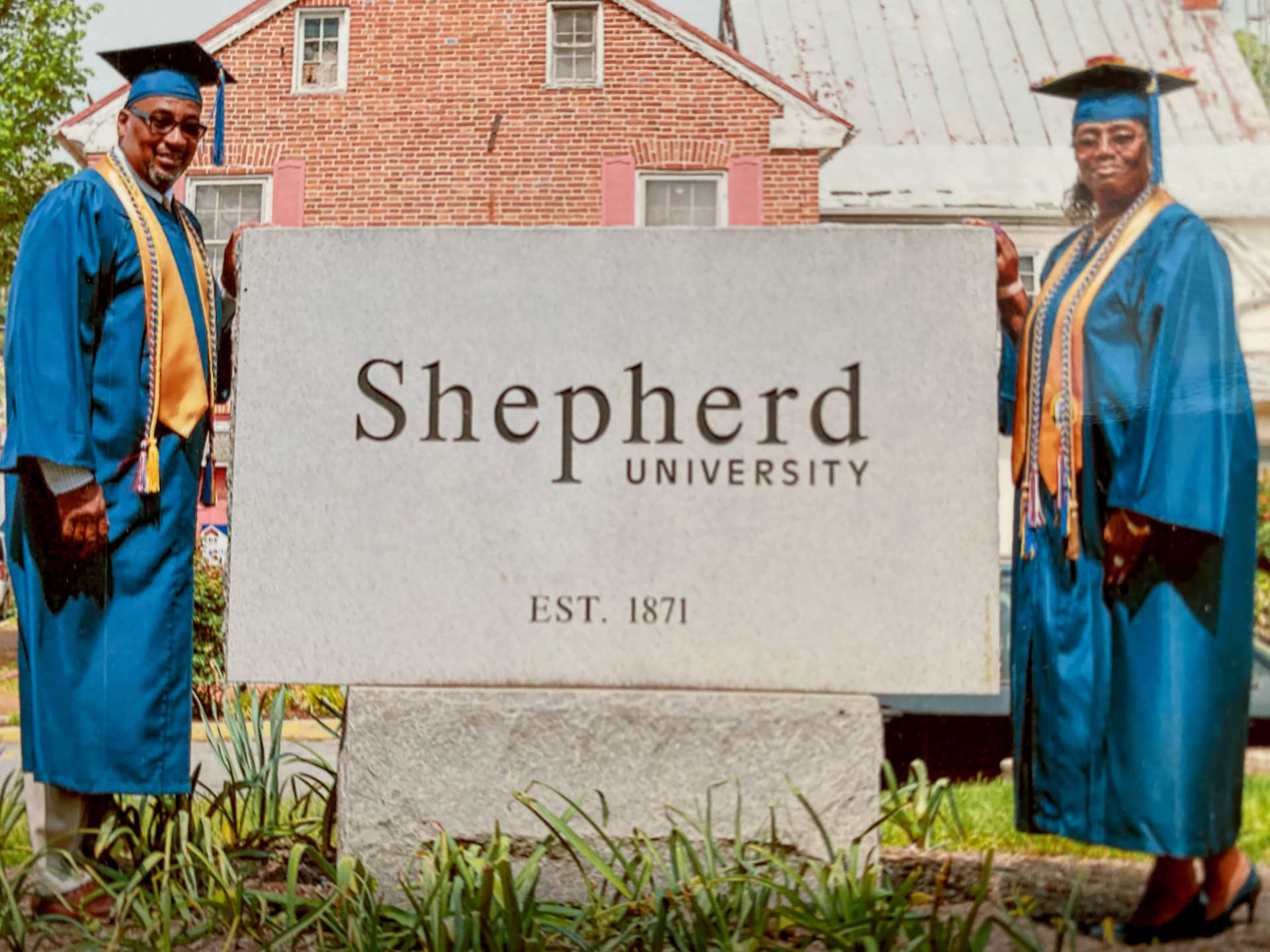 Osmund Anderson and Debra Saunders pose in their caps and gowns next to Shepherd's sign.