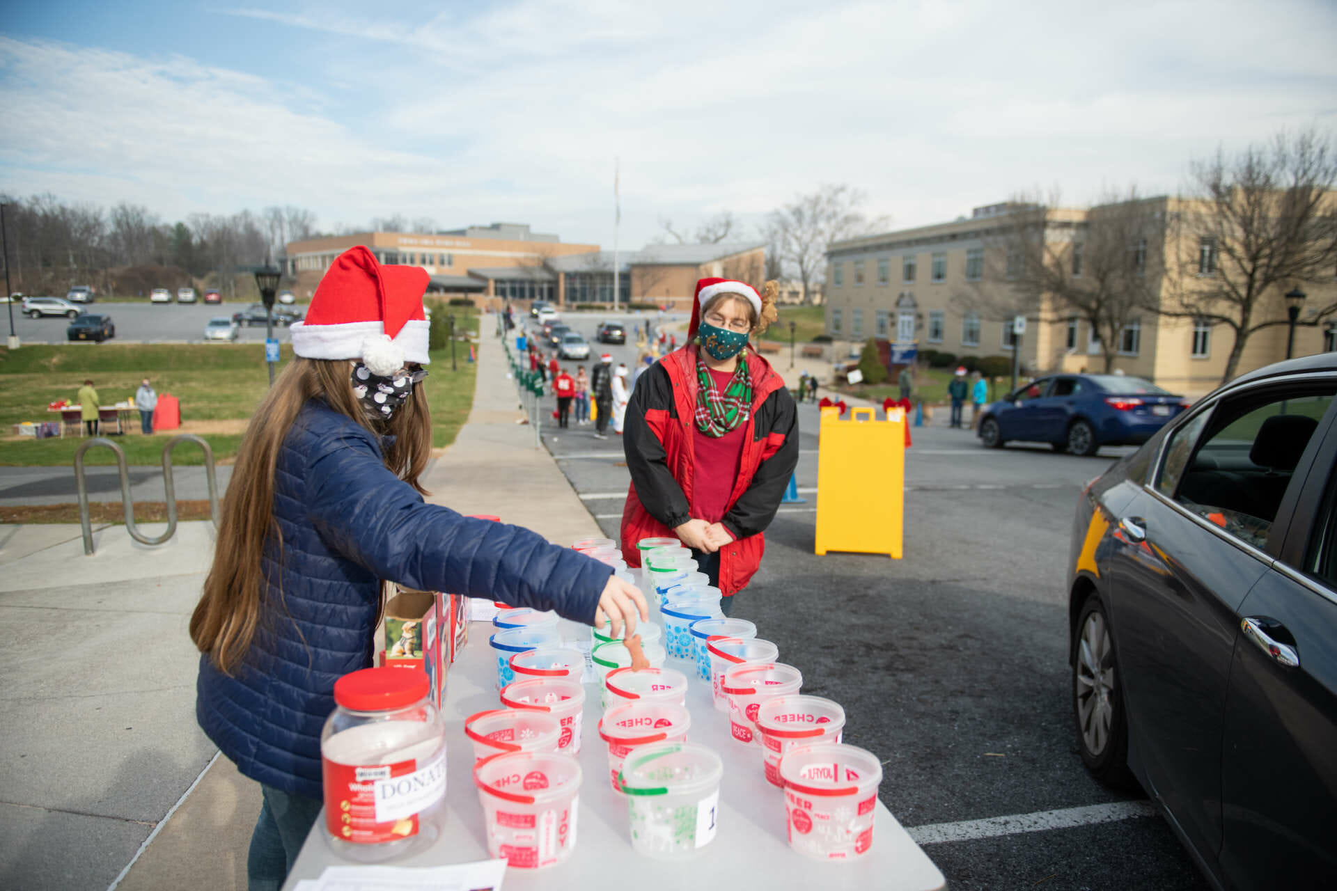 """After driving past all the contestants in the """"Best in Howliday Show,"""" attendees vote on their favorite by having a dog treat dropped in a cup labeled with the contestant's number. Photo by Seth Freeman."""