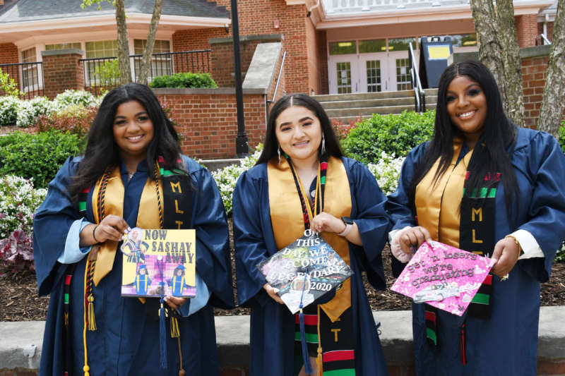 three students wearing MLT stoles and showing off their graduation caps