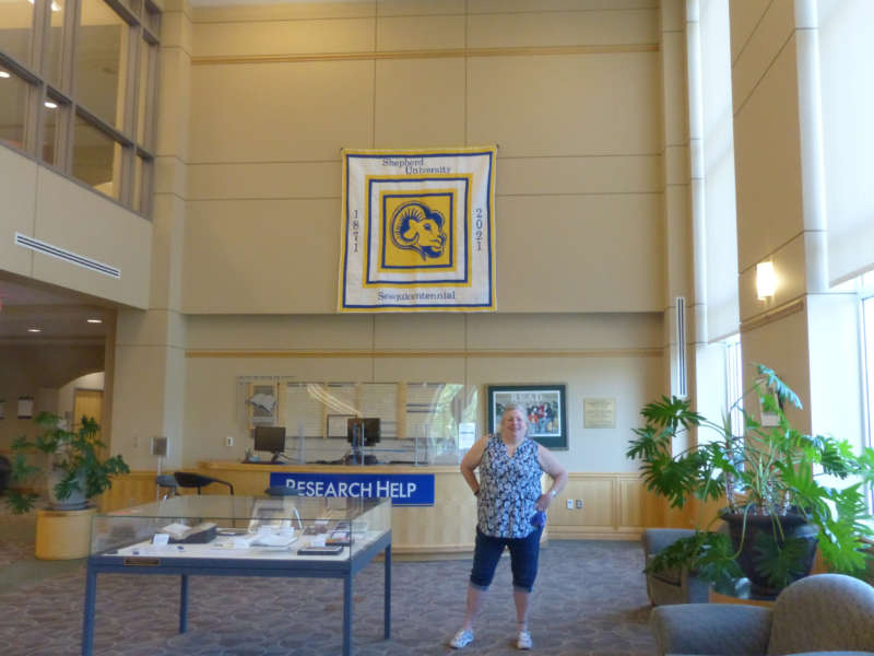 Rhonda Donaldson, Scarborough Library coordinator of research services, stands in front of a queen-size quilt she made to commemorate Shepherd's sesquicentennial that is hanging in the library.