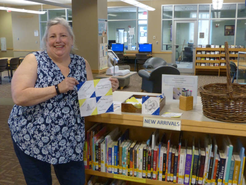 Rhonda Donaldson, Scarborough Library coordinator of research services, holds a set of completed squares for the signature quilt she will sew.