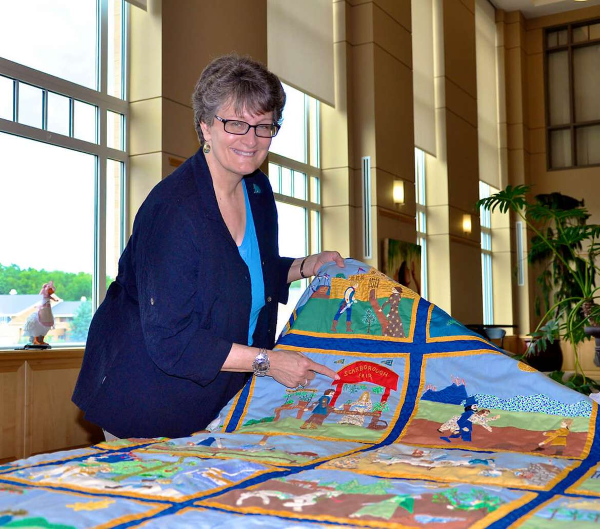 Dr. Martha Dolly presents a special handmade Appalachian quilt from her mother, Phyllis Nichols Rowe.
